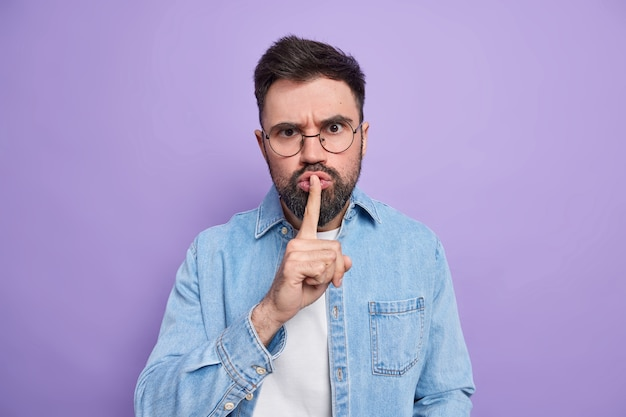 Serious bearded young man demands keep silence presses finger to lips makes hush gesture asks to keep mouth shut spreads rumors wears round spectacles denim shirt isoated over purple wall