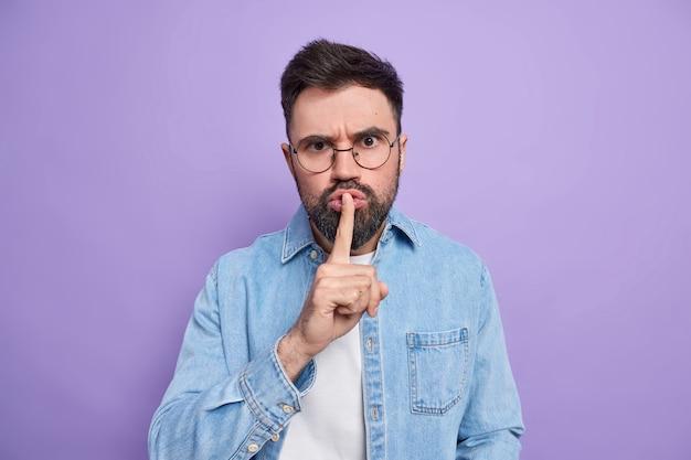 Серьезный бородатый молодой человек требует молчать, прижимает палец к губам, делает жест молчания, просит держать язык за зубами, распространяет слухи, носит круглые очки, джинсовая рубашка над фиолетовой стеной