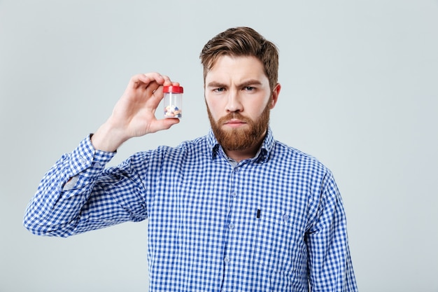 Serious bearded young man holding pills in bottle over white wall