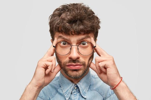 Серьезный бородатый молодой человек держит пальцы на висках, пытается вспомнить что-то важное, выглядит напряженно.