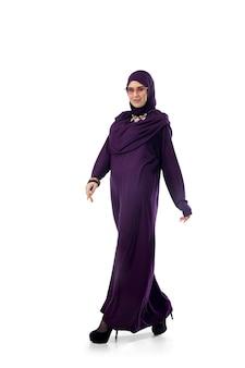심각한. 광고용 카피스페이스가 있는 스튜디오 배경에서 세련된 히잡을 쓰고 포즈를 취하는 아름다운 아랍 여성. 패션, 뷰티, 스타일 컨셉입니다. 트렌디한 메이크업, 매니큐어, 액세서리를 갖춘 여성 모델.