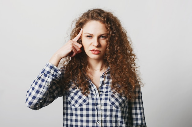 Serious beautiful curly woman keeps finger on temple as tries to remember some details