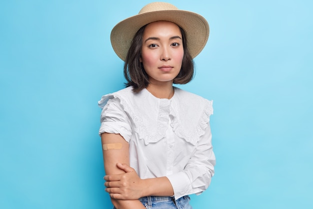 Serious beautiful dark haired asian woman wears sunhat and white blouse shows arm with plaser after successful covid vaccination models against blue wall