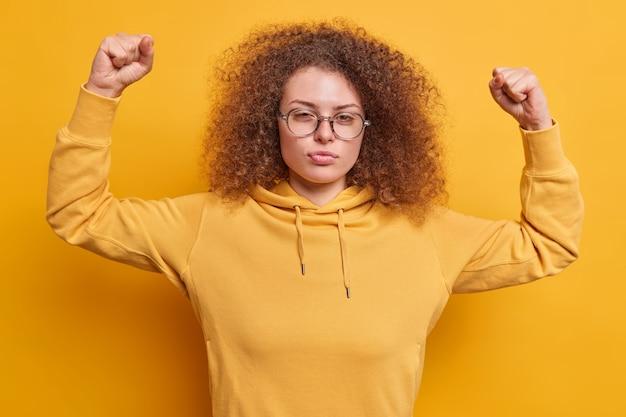 巻き毛の真面目な美しいヨーロッパ人は自信を持って腕を上げ、筋肉が眼鏡をかけ、黄色の壁に隔離されたスウェットシャツが強さについて強い自慢をしていることを示しています