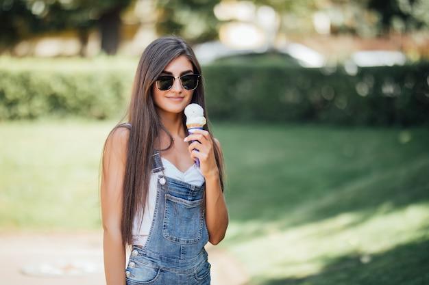 Серьезная красивая девушка улыбается с белыми зубами и держит мороженое