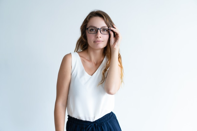 Serious beautiful lady adjusting glasses and looking at camera