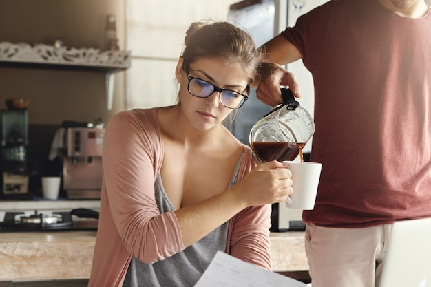 Serious beautiful young caucasian woman wearing stylish glasses studying paper, managing family budget in kitchen while her husband standing next to her and pouring fresh coffee into her cup