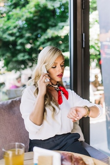 Serious beautiful young woman talking on the cell phone looking at her wrist watch