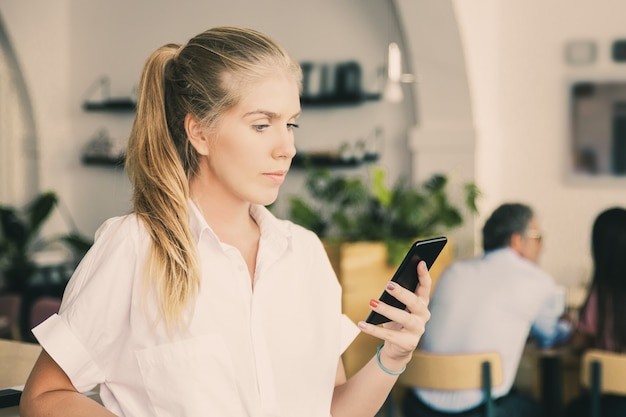 Serious beautiful young woman wearing white shirt, using smartphone, typing message, standing in co-working space