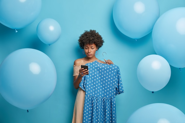 Serious birthday girl receives congratulation on smartphone, picks blue polka dot dress on hanger, gets dressed and waits for guests, stands against decorated wall. women, clothes, dressing