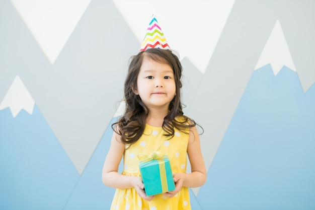 Serious birthday girl with small gift box