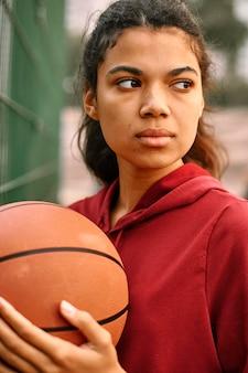 Серьезная темнокожая американская женщина играет в баскетбол
