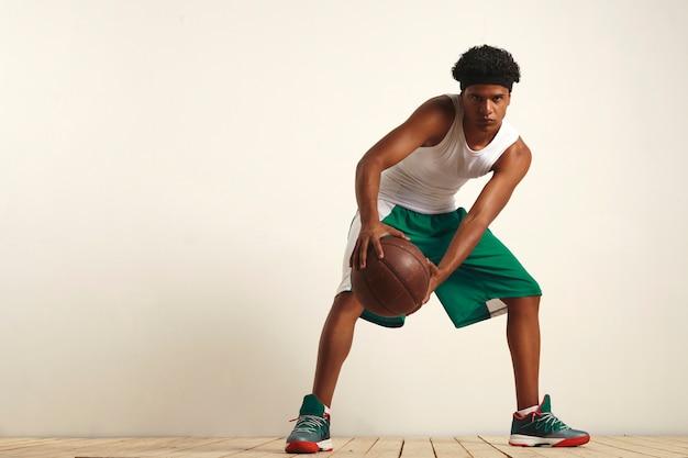 Grave atleta nero in verde e bianco con un pallone da basket vintage tenuto contro il ginocchio