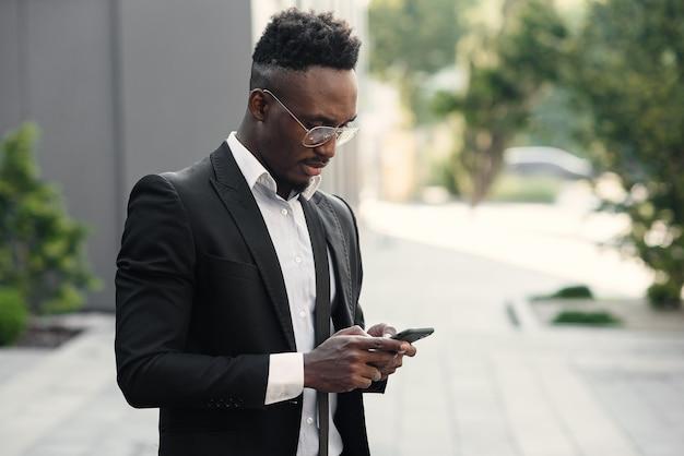 屋外のスマートフォンで深刻な黒人実業家のテキストメッセージ