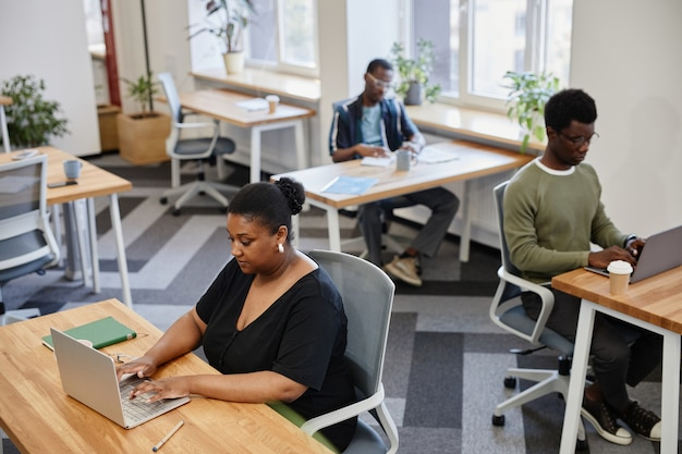 Serious black businesswoman renting desk in open space coworking center