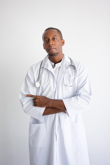 Serious black male doctor pointing aside. Medical service advertising concept.