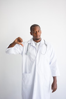 Serious black male doctor showing thumb down. Harm to health concept.