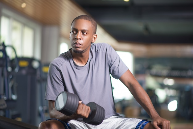 Serious black man exercising with dumbbell