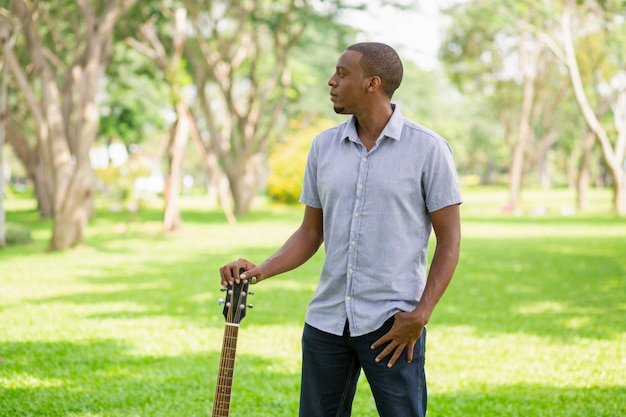 Serious black man holding guitar by headstock in park