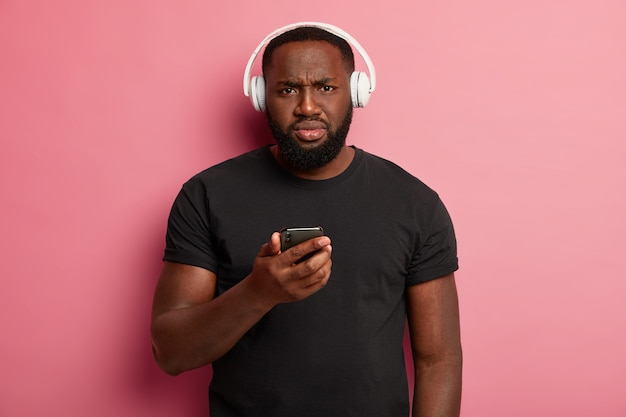 Serious black man with displeased expression uses wireless headphones
