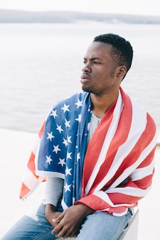 Serious black man wrapped in american flag sitting on beach