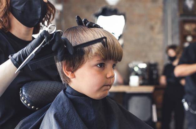 マスクをした女性美容師によって美容院でスタイリングされている深刻なブロンドの少年