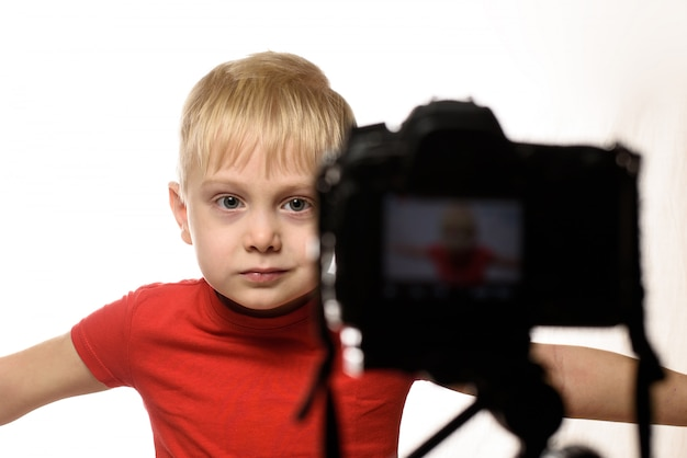 Serious blond boy is recording a video on dslr camera.