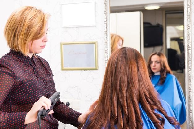 バックグラウンドミラーでクライアントの反射とサロンでブルネットの女性の髪にフラットアイロンを使用して深刻なブロンドのスタイリスト