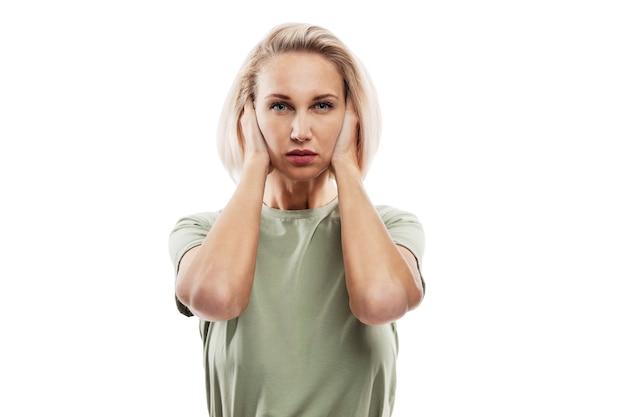 彼女の手で彼女の耳を覆っている深刻なブロンドの女性。社会恐怖症と心理的問題。白い壁に隔離。