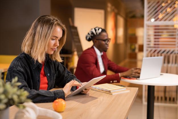 Серьезная блондинка в повседневной одежде сидит за столиком в кафе колледжа и прокручивает тачпад на перерыве