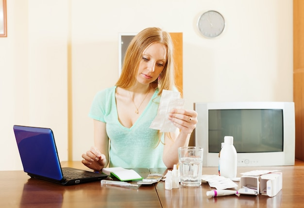 Serious blonde woman reading about medications
