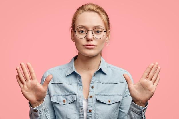 自信を持って表情を見せ、手のひらを見せ、ジェスチャーを止め、何かをすることを許さず、ファッショナブルな服を着て、ピンクの壁に隔離された真面目なブロンドの女性