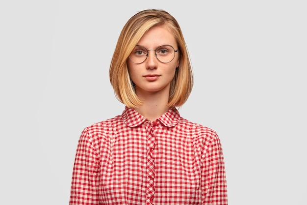 Serious blonde woman with trendy hairstyle, looks seriously at camera, dressed in fashioble red checkered blouse
