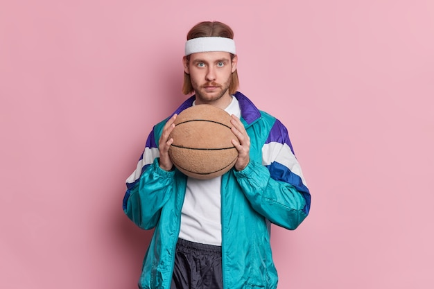 Serious blue eyed male basketball player with stubble long hair holds ball ready for playing game wears white headband and sportsclothes.