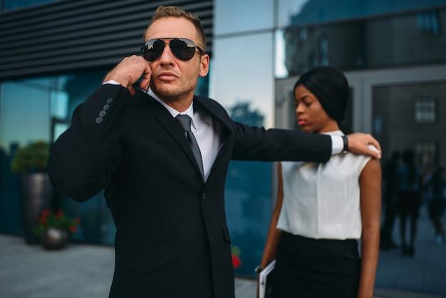 スーツとサングラスの深刻なボディーガードは、女性のクライアントを保護するためにイヤホンのサポートを要求します。