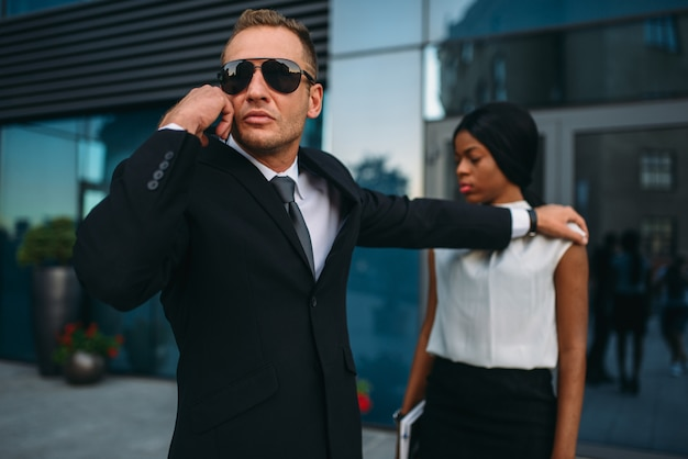 Serious bodyguard in suit and sunglasses requests support on earpiece for female client protection.