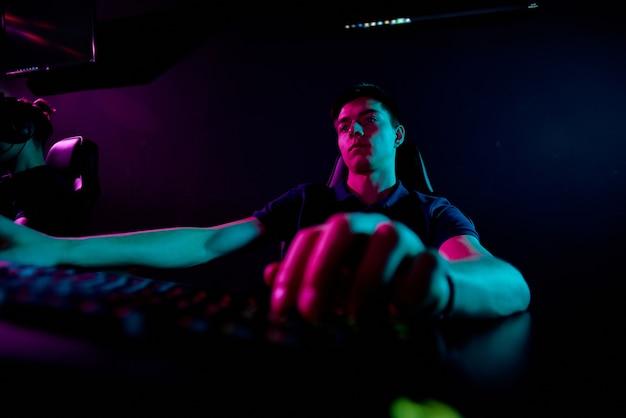 Серьезный скучный молодой человек сидит за столом и играет в видеоигры или кодирует скрипт для нового приложения