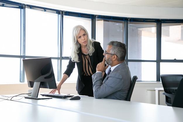 심각한 상사와 관리자가 보고서를 논의하고 앉아 파노라마 창으로 직장에 서있는 동안 이야기합니다. 비즈니스 커뮤니케이션 개념