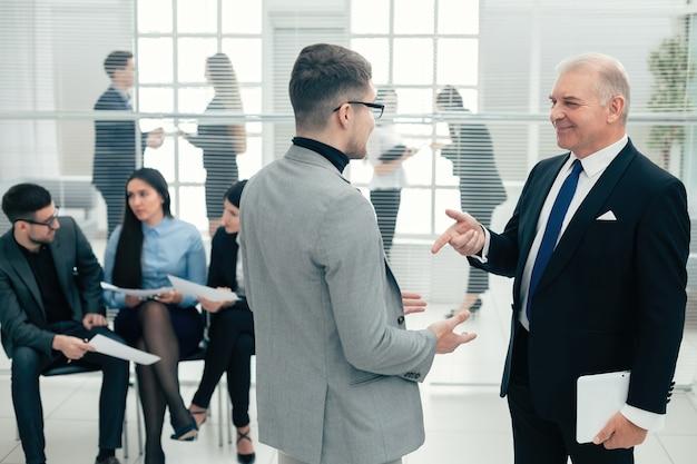 Серьезный босс что-то объясняет своему помощнику. рабочие будни в офисе
