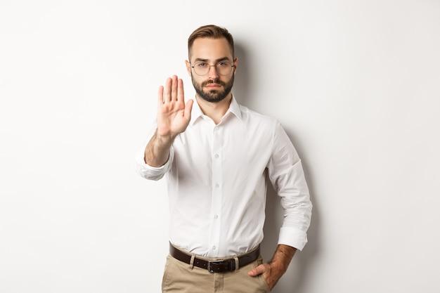 Серьезный босс в очках показывает знак остановки, говорит нет, что-то запрещает, стоит белым