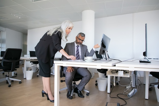 Serious boss and manager analyzing reports together, talking while sitting and standing at workplace, pointing hand at pc monitor. business communication concept
