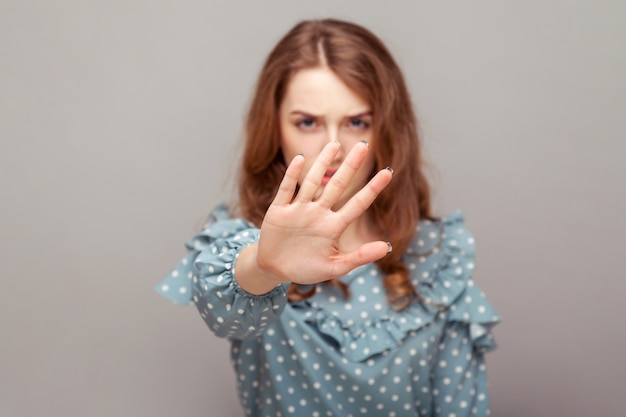 Serious bossy girl ruffle blouse keeping outstretched hand up, showing stop no prohibition gesture