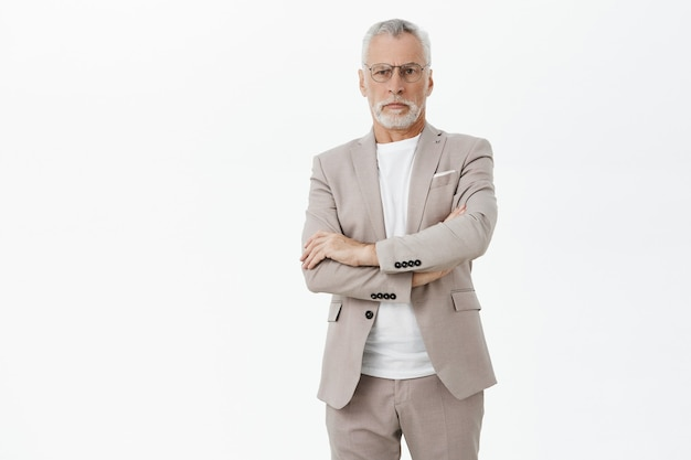 Serious bossy old businessman cross arms and looking confident