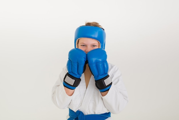 Serious boxer boy wearing a helmet and gloves stands in a pose on a white wall