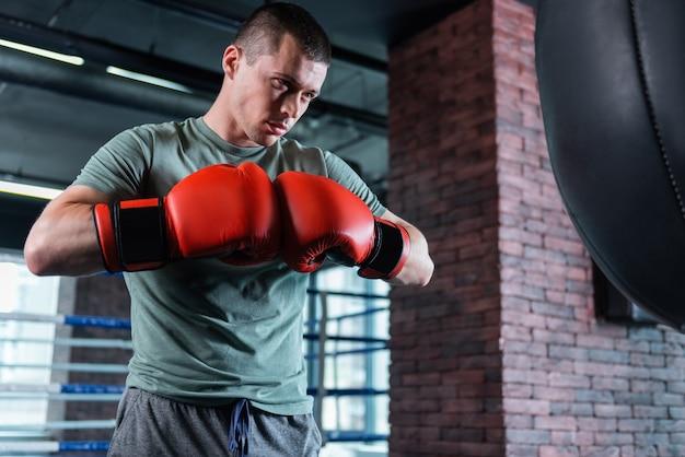 Serious boxer. serious dark-eyed famous boxer feeling joyful while working out near punching bag