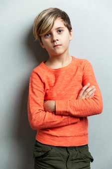 A serious boy of 9 years old in an orange jacket stands against the wall. the arms are crossed over the chest. gray background. vertical.