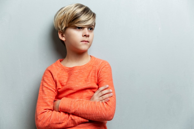 A serious boy of 9 years old in an orange jacket stands against the wall. the arms are crossed over the chest. gray background.