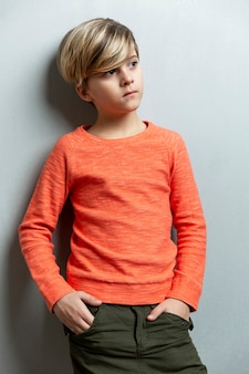 A serious boy of 9 years old in an orange jacket stands against the wall. hands in pockets. gray background. vertical.