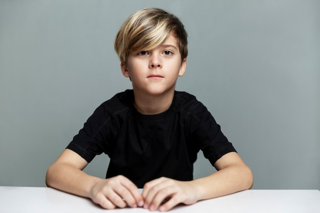 A serious boy of 9 years old with a fashionable hairstyle in a black t-shirt sits at the table.
