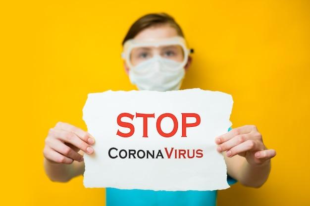 Серьезный мальчик-девочка в защитной маске во время карантина и пандемии в мире из-за covid-19 остался дома и держит плакат с призывом «остановить коронавирус».